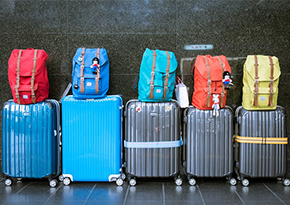 five coloured suitcases on wheels with a backpack stacked on top of each one