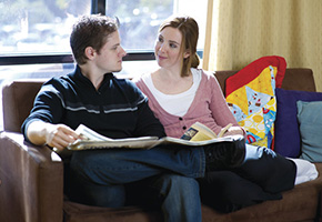 Young man and woman sitting on couch talking