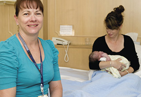 Nurse with new mother in hospital with her new born baby