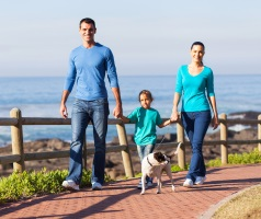 Family walking with dog at beach